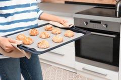 Jonge vrouw met bladpan van oven gebakken koekjes in keuken stock afbeelding