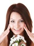 Jonge vrouw met bloem. Gezichts massage. stock foto