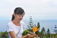 Jonge vrouw met bloem van Strelitzia Stock Afbeeldingen