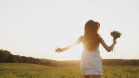 Jonge vrouw met bloemboeket in witte kleding die het gebied bij zonsondergang, het genieten doornemen van stock videobeelden