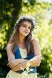 Jonge vrouw met bloemkroon op haar hoofd Stock Afbeeldingen