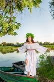 Jonge vrouw met bloemkroon op haar hoofd, die op boot op rivier bij zonsondergang ontspannen Concept vrouwelijke schoonheid, rust stock fotografie