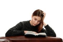 Jonge vrouw met boek die op leermeubilair leunen Royalty-vrije Stock Afbeeldingen