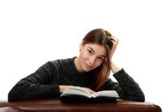 Jonge vrouw met boek die op leermeubilair leunen Stock Fotografie