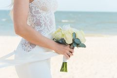 Jonge vrouw met boeket van bloemen op het strand stock afbeeldingen