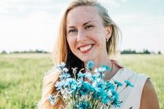 Jonge vrouw met boeket van korenbloemen stock fotografie