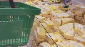 Jonge vrouw met boodschappenwagentje die tot de koelkast in winkel komen en product nemen uit het Meisjes uitgezochte kaas in stock videobeelden