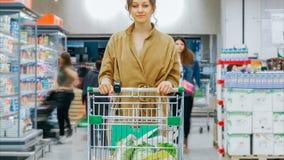 Jonge vrouw met boodschappenwagentjetribunes in supermarkt stock videobeelden