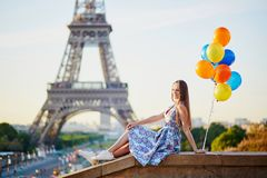 Jonge vrouw met bos van ballons dichtbij de toren van Eiffel stock foto