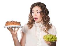 Jonge vrouw met cake en geïsoleerdeu druiven royalty-vrije stock fotografie