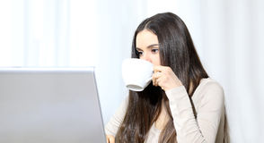 Jonge vrouw met computer en kop ter beschikking stock foto's