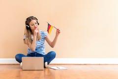 Jonge vrouw met de vlag die van Duitsland een laptop computer met behulp van royalty-vrije stock afbeeldingen