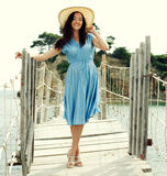 Jonge vrouw met de zomerhoed het stellen op de brug Royalty-vrije Stock Afbeelding