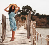 Jonge vrouw met de zomerhoed het stellen op de brug Royalty-vrije Stock Afbeeldingen