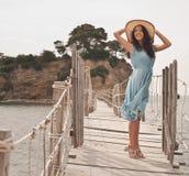 Jonge vrouw met de zomerhoed het stellen op de brug Stock Afbeeldingen