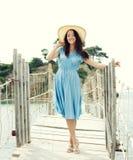 Jonge vrouw met de zomerhoed het stellen op de brug Royalty-vrije Stock Foto's