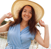 Jonge vrouw met de zomerhoed het stellen op de brug stock fotografie