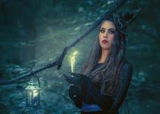 Jonge vrouw met een brandend boek in het bos stock afbeelding