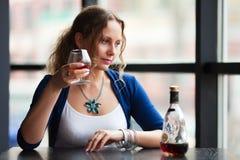 Jonge vrouw met een cognac. stock foto