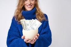 Jonge vrouw met een ei en een geld ter beschikking royalty-vrije stock foto