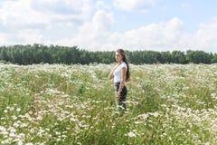 Jonge vrouw met een gebied met madeliefjes Royalty-vrije Stock Afbeelding