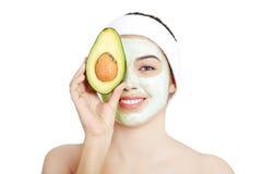 Jonge vrouw met een glimlachholding met avocado Royalty-vrije Stock Afbeeldingen