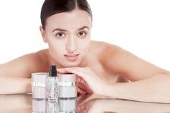 Jonge vrouw met een goed-verzorgde huid dichtbij de roomschoonheidsmiddelen. Stock Foto