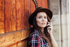Jonge vrouw met een hoed naast een oude houten deur die bij cel spreken Stock Foto's