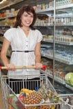 Jonge vrouw met een karretje bij een supermarkt Stock Foto