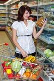 Jonge vrouw met een karretje bij een supermarkt Stock Afbeelding