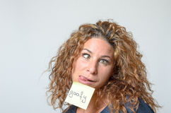 Jonge vrouw met een kleverige nota in haar gezicht Stock Afbeeldingen