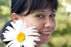 Jonge vrouw met een madeliefje Stock Fotografie