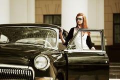 Jonge vrouw met een retro auto. Stock Foto's