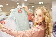 Jonge vrouw met een selectie van T-shirts stock foto