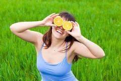 Jonge vrouw met een sinaasappel Stock Foto's