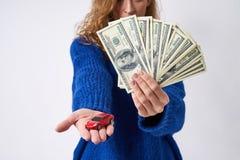 Jonge vrouw met een een stuk speelgoed auto en geld ter beschikking royalty-vrije stock foto