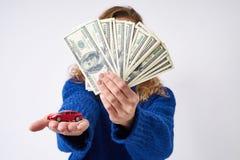 Jonge vrouw met een een stuk speelgoed auto en geld ter beschikking royalty-vrije stock fotografie