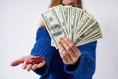 Jonge vrouw met een een stuk speelgoed auto en geld ter beschikking stock foto