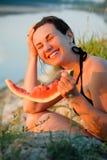 Jonge vrouw met een watermeloen op rivierbank Stock Foto