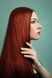 Jonge vrouw met elegant lang rood glanzend haar. Stock Afbeelding