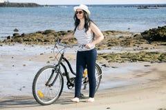 Jonge vrouw met fiets op kust Stock Afbeelding