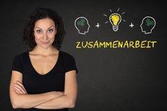 Jonge vrouw met gekruiste wapens, hoofden, bol-idee & tekst 'Zusammenarbeit 'op een bord Vertaling: & x27; Teamwork& x27; stock foto