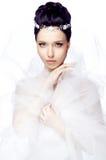 Jonge vrouw met gesloten die ogen op witte studioachtergrond gekleed wordt geïsoleerd in de kaap van organza en mooie tiara Stock Foto's