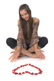 Jonge vrouw met gevormd hart dat van roze bloemblaadjes wordt gemaakt Royalty-vrije Stock Afbeeldingen
