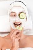 Jonge vrouw met gezichtsmasker en komkommer Royalty-vrije Stock Foto