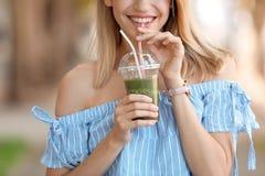 Jonge vrouw met gezonde smoothie in openlucht royalty-vrije stock afbeeldingen