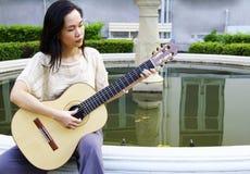 Jonge vrouw met gitaar Stock Afbeelding