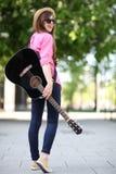 Jonge vrouw met gitaar Stock Foto's