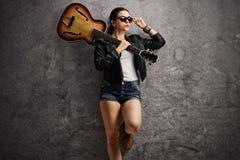 Jonge vrouw met gitaar op haar schouder die op roestige grijze wa leunen Stock Afbeeldingen