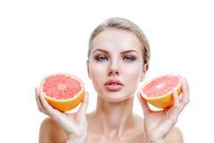 Jonge vrouw met grapefruit in handen Stock Fotografie